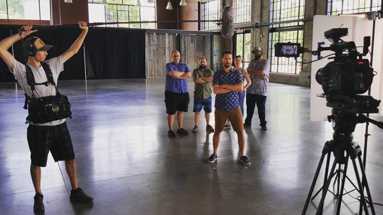 un groupe dans une salle de studio aéré devant une caméra avec un preneur de son qui tend sa perche.
