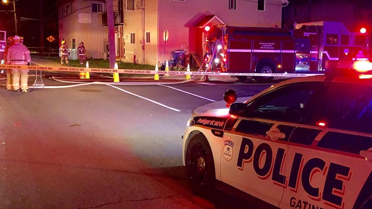 Des voitures de police et des camions de pompiers sont stationnés à proximité de l'immeuble.