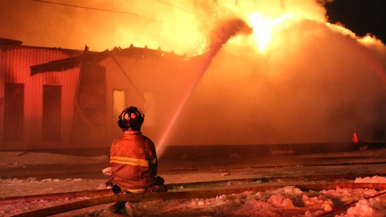 Un pompier accroupi par terre arrose un bâtiment industriel en feu en hiver