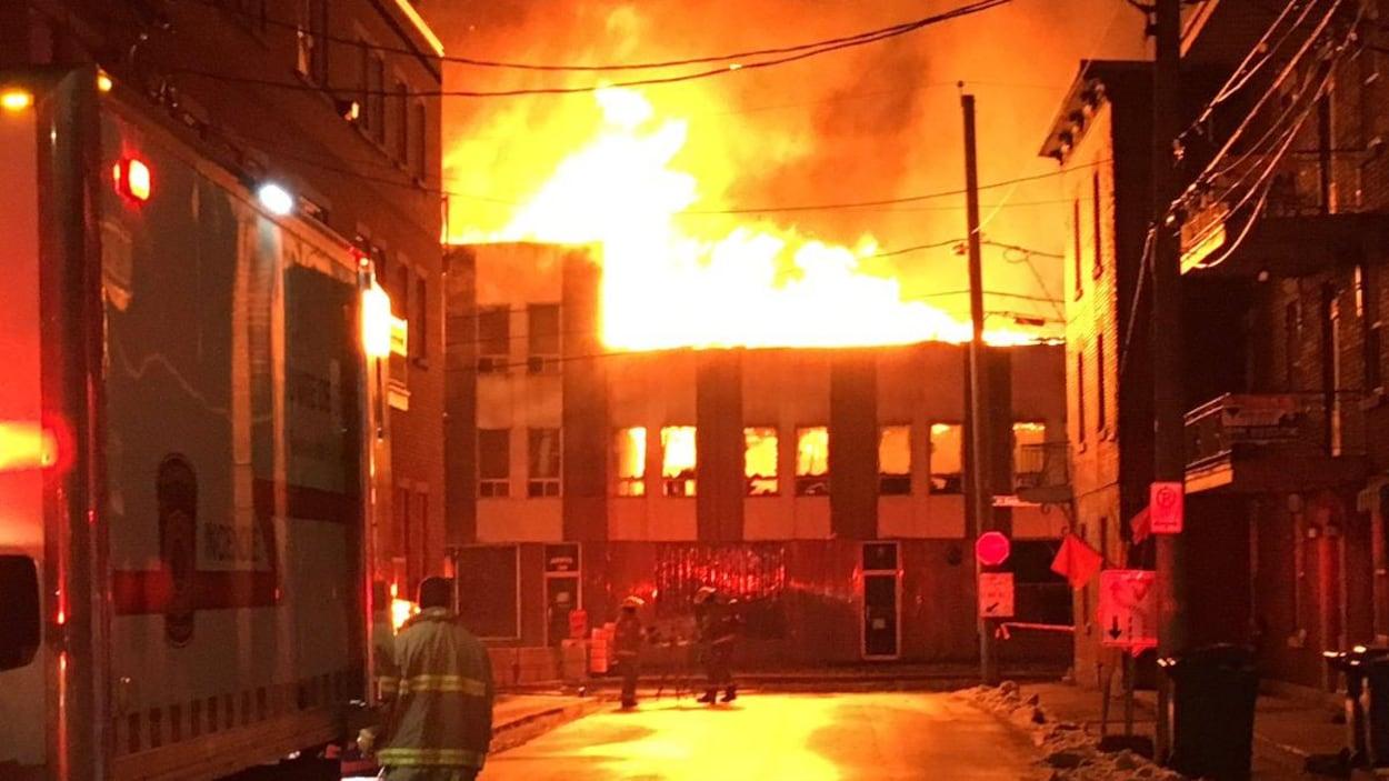 Un pompier regarde les flammes qui ravage au loin les locaux de l'ancienne Crémerie de Trois-Rivières