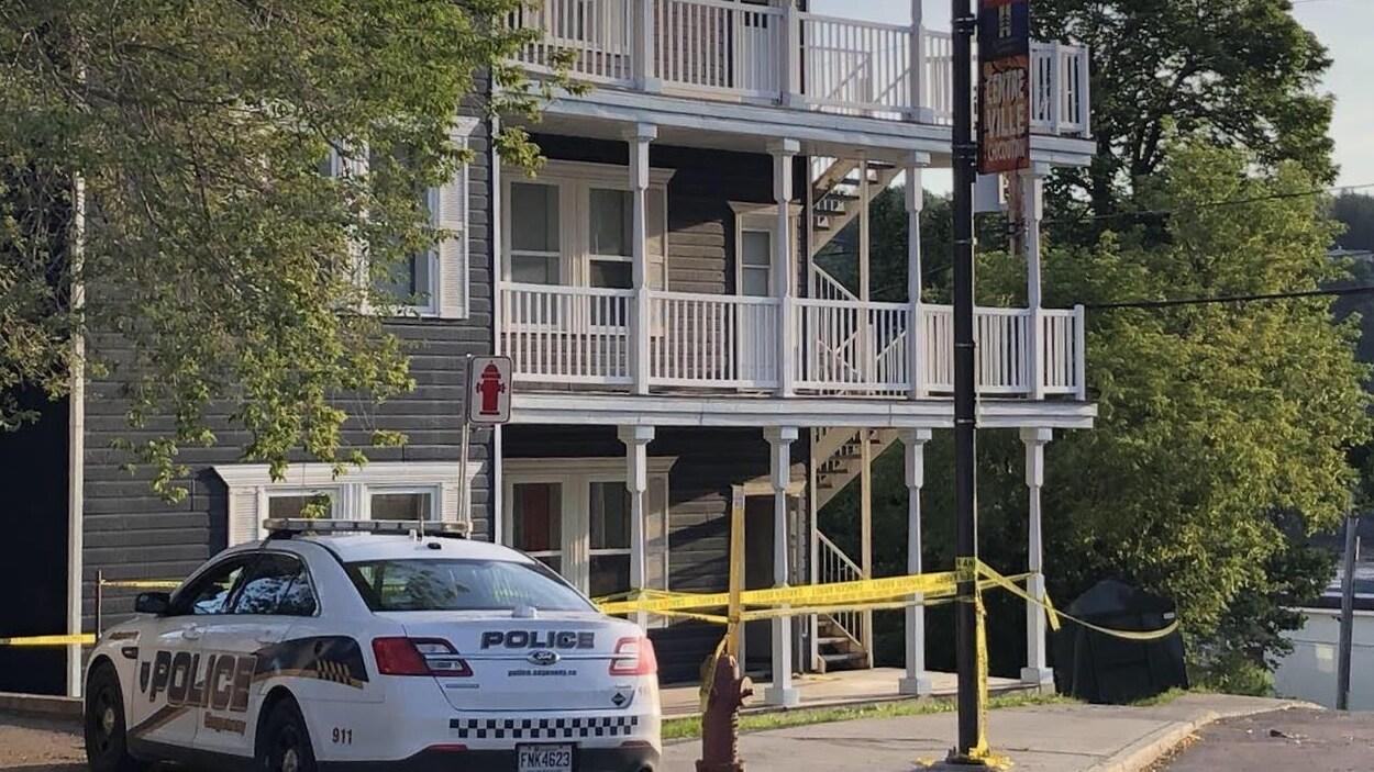 Une voiture de patrouille stationnée devant un immeuble à logements entouré d'un périmètre de sécurité.