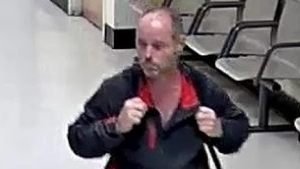 l'homme est peu visible, mais il a une calvitie, porte un chandail qui semble noir avec un col rouge et un sac à dos qu'il tient des deux mains, il paraît avoir une quarantaine d'années environ