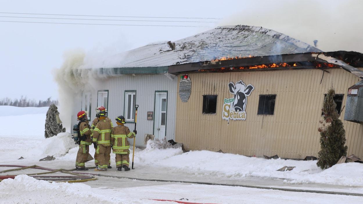 Les pompiers de Lévis qui tentent d'éteindre l'incendie d'un bâtiment de ferme du secteur Pintendre.