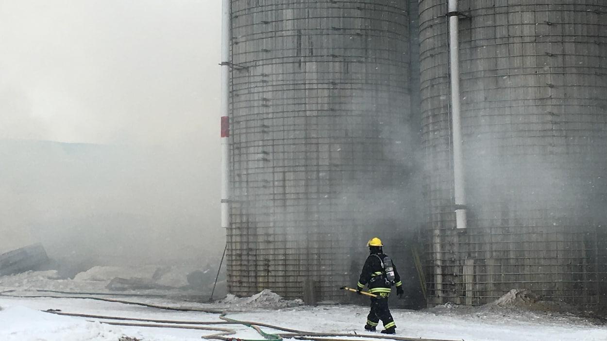 Pompier devant des silos enfumés