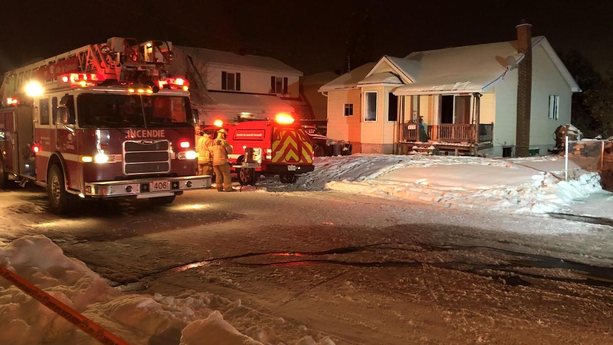 Deux camions de pompiers stationnés devant une résidence de Gatineau.
