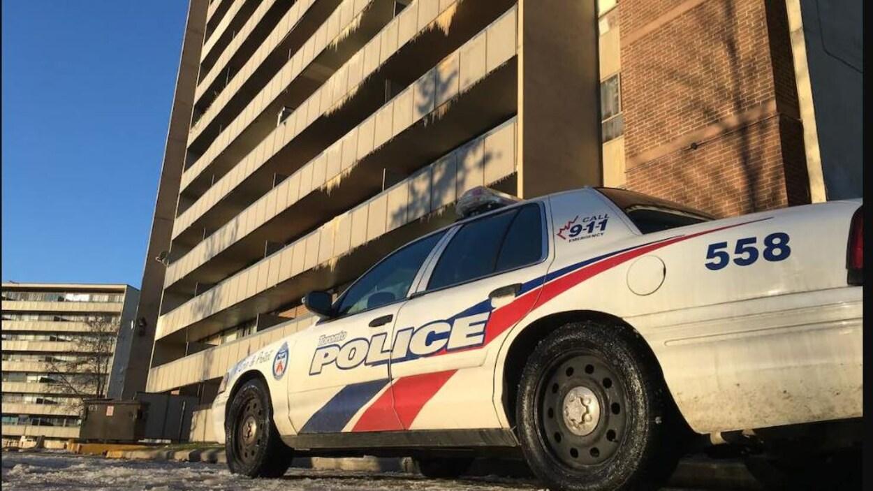 Une autopatrouille de la police de Toronto stationné devant une grand tour d'habitation, marquée par l'incendie.