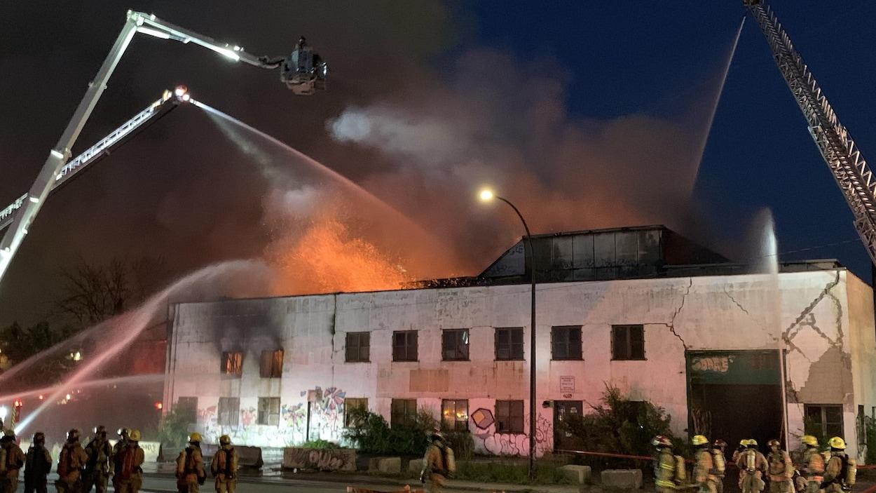 Des pompiers autour d'un bâtiment en feu.