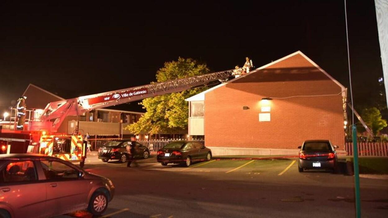 Deux pompiers sur une grande échelle sur le toit d'une résidence.