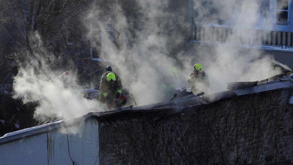 Les pompiers rabattent les flammes sur le toit de l'immeuble.