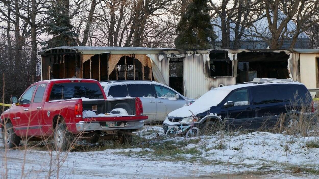 Un camion de style pick-up et deux camionnettes sont stationnés devant la structure d'une maison modulaire incendiée.