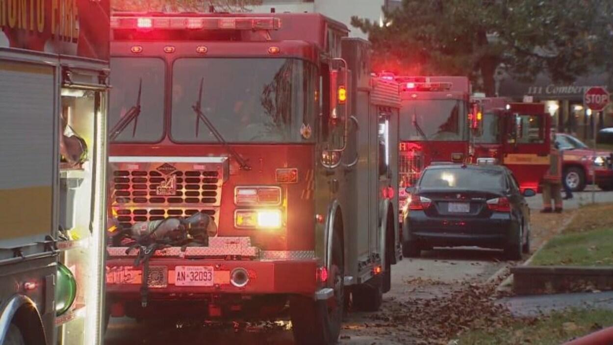 Des camions de pompiers dans une rue résidentielle.