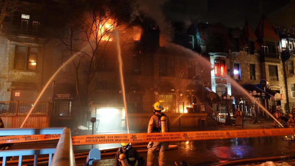 Des pompiers tentent de maîtriser le feu qui a éclaté dans un bâtiment commercial dans le centre-ville de Montréal.