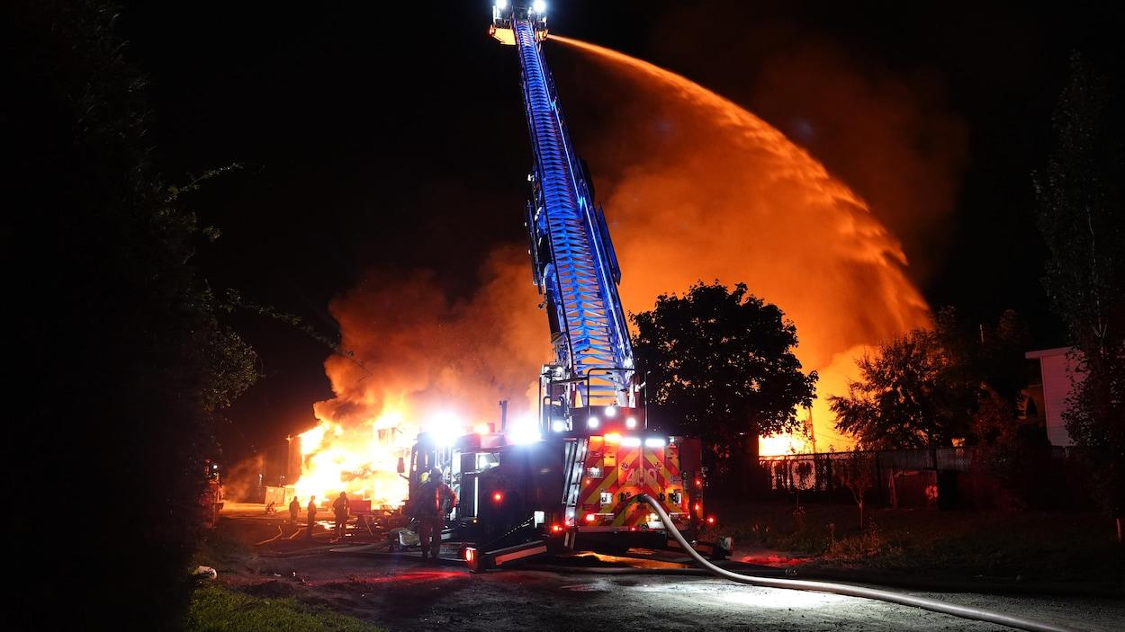 Les pompiers arrosent un gros incendie de la grande échelle d'un camion de pompier.