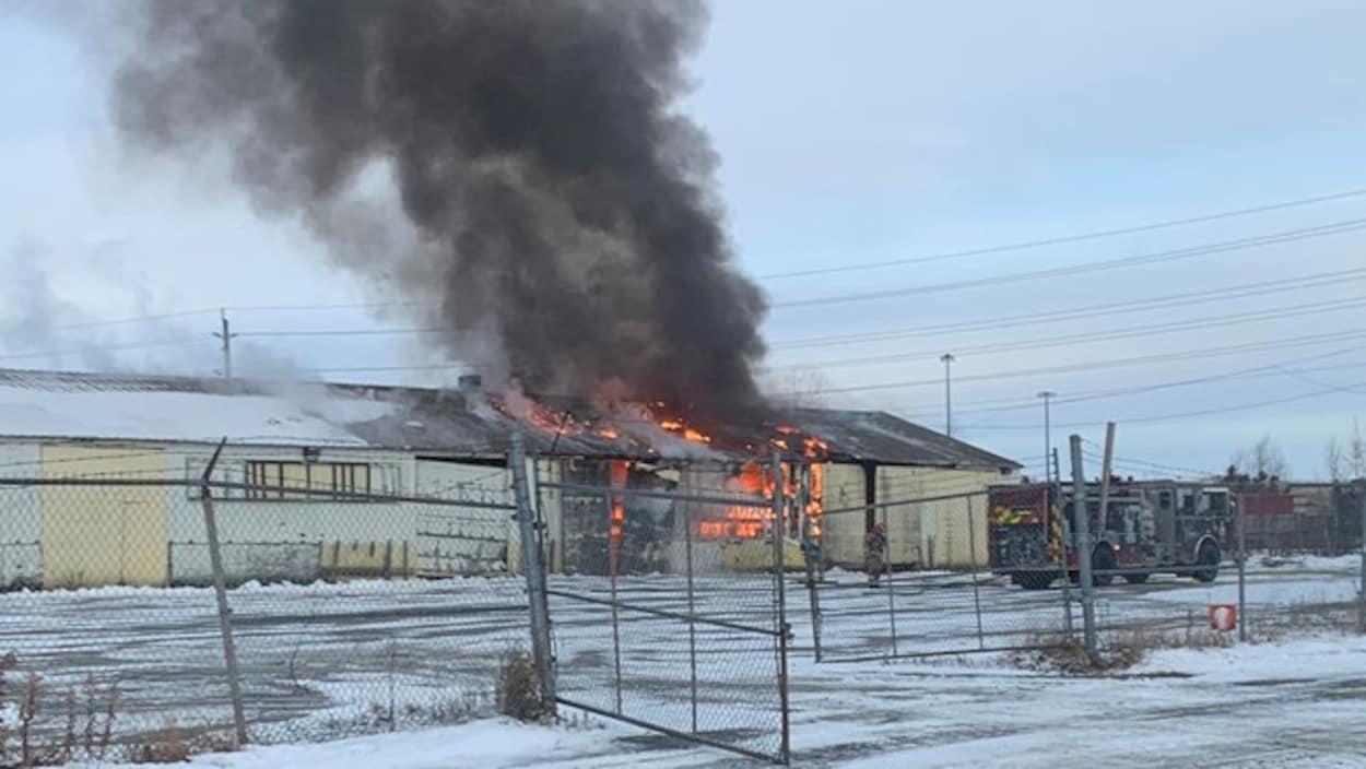 De la fumée noire qui s'échappe d'un bâtiment en flamme.