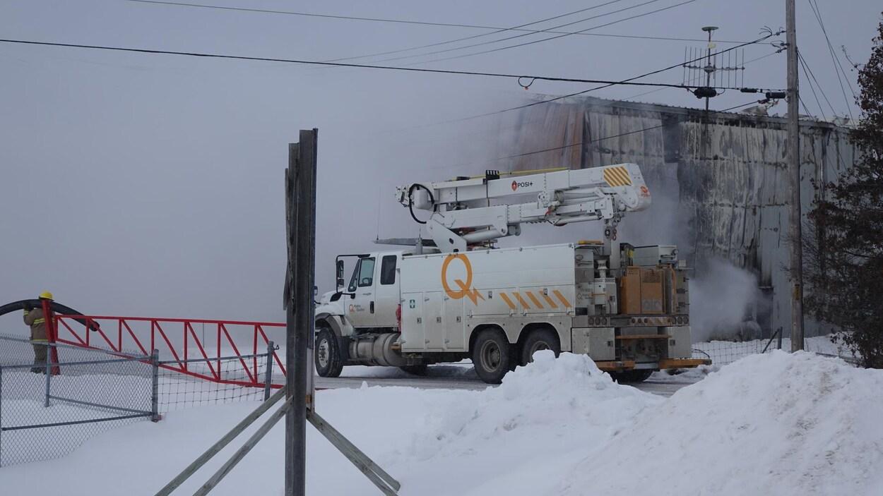 Un pompier et un camion d'Hydro-Québec devant un bâtiment enveloppé de fumée.