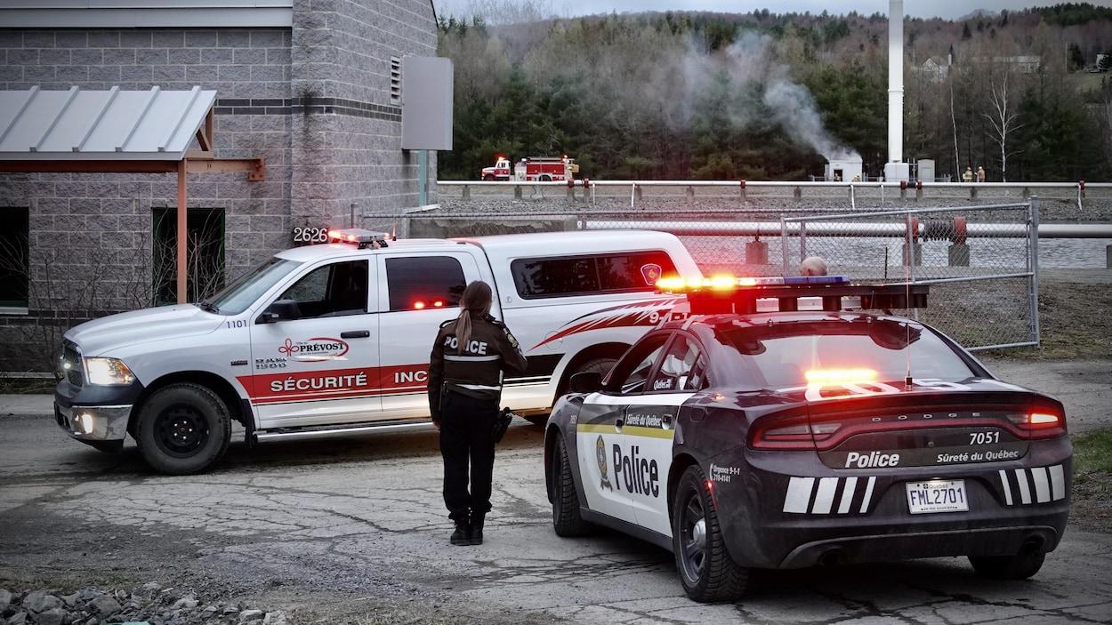 Une policière près de son autopatrouille observe des pompiers qui s'affairent autour d'une tour de télécommunication. Une fumée blanche sort d'une cabane située tout près de la tour.