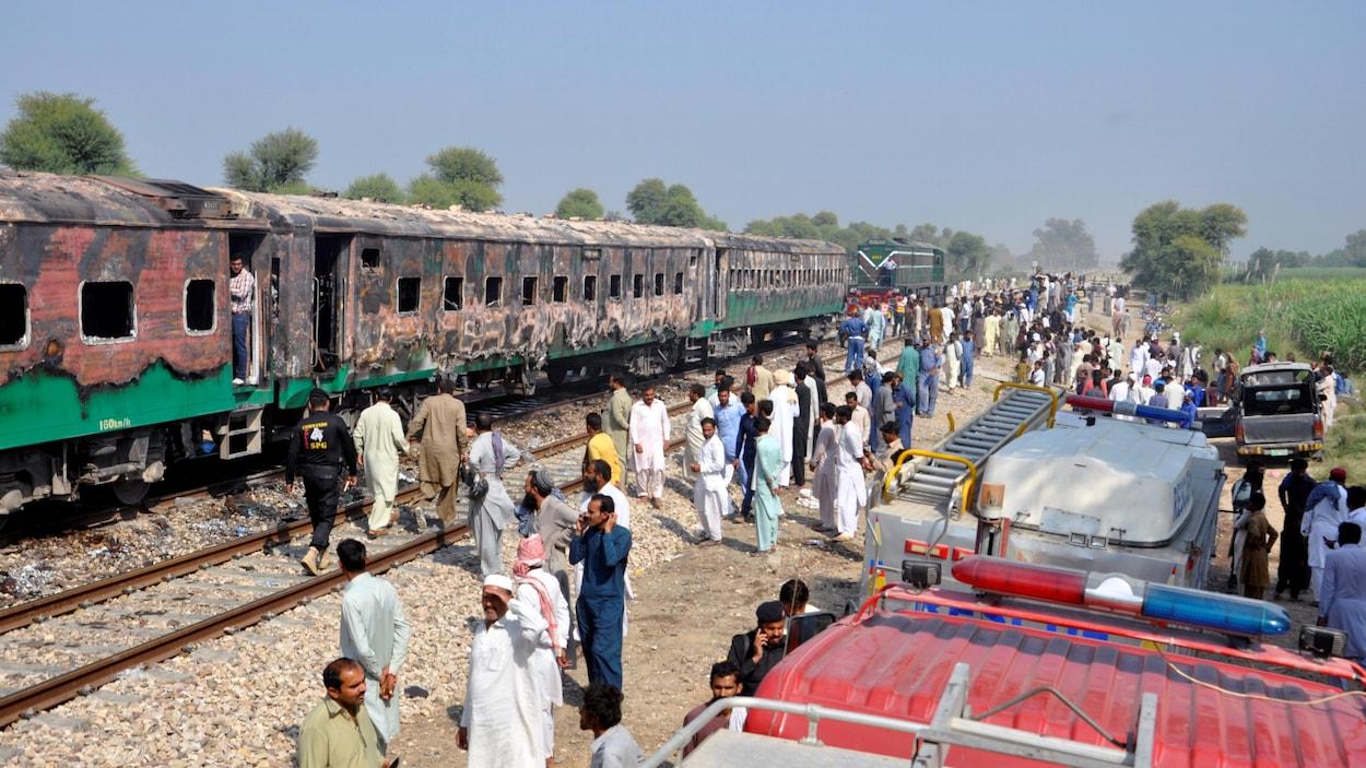 Des dizaines de personnes, voire des centaines, entourent la carcasse calcinée du train.