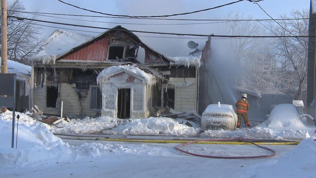 Maison glacée avec un pompier qui arrose.