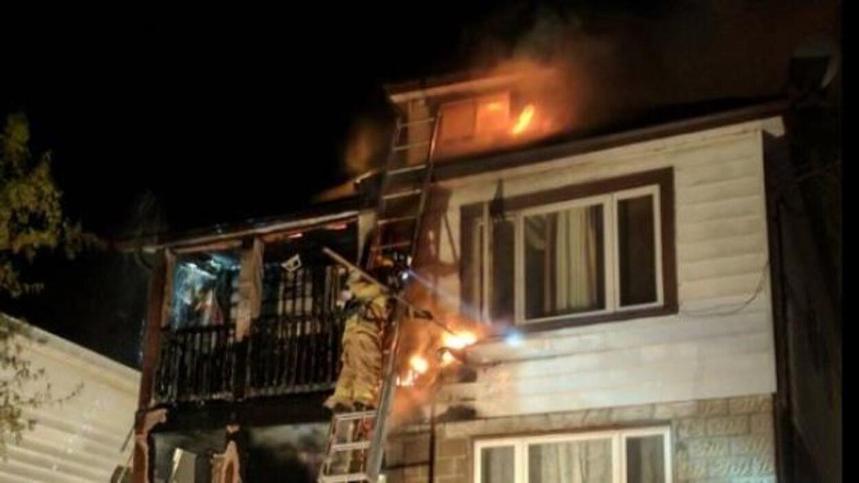 Un pompier sur une échelle devant le second étage d'un logement en flammes.
