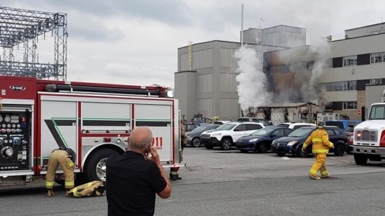 Homme au téléphone devant un camion de pompier et une usine où on observe des colonnes de fumées qui sortent de la bâtisse,