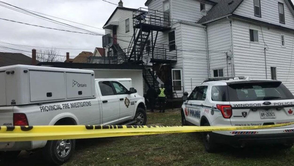 Des véhicules de police et du gouvernement de l'Ontario garés devant une maison