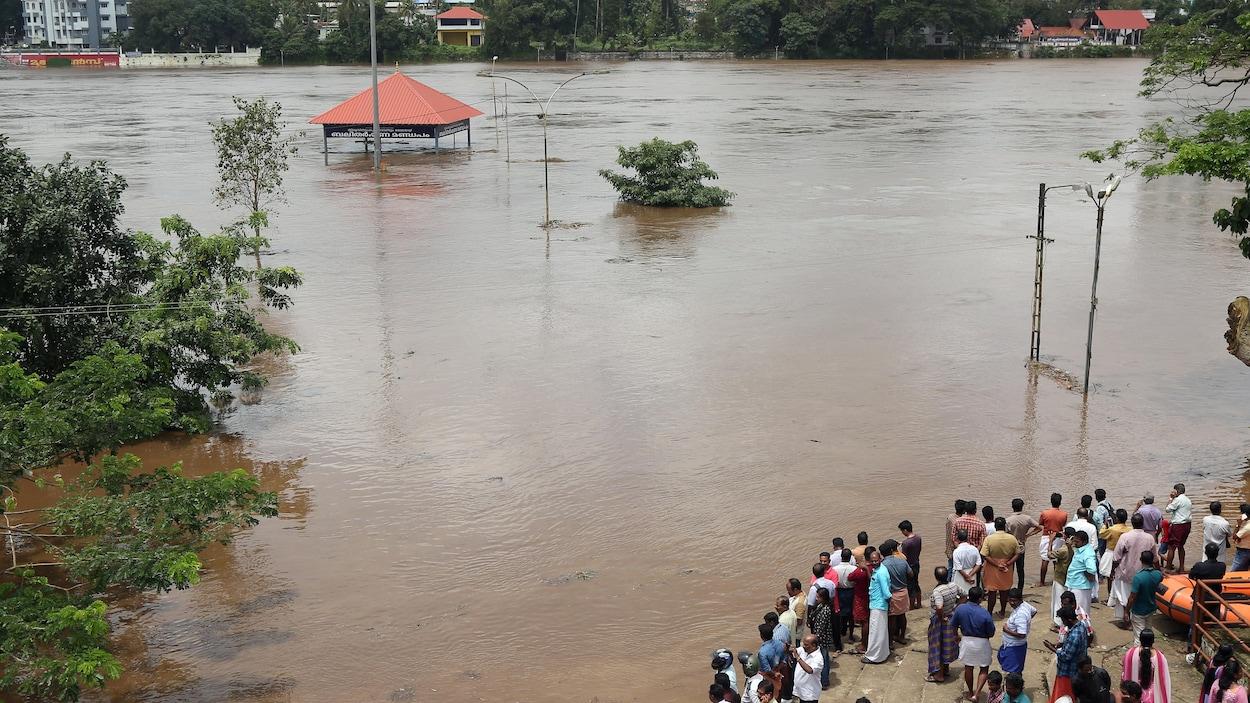 Des Indiens sur le parvis du temple Aluva Shiva inondé.