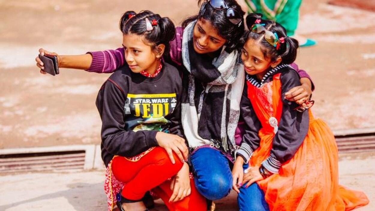 Des filles se photographient en selfie dans une rue de New Delhi