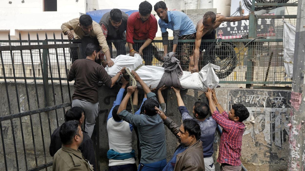 Des hommes descendent un cadavre recouvert d'un drap afin que d'autres hommes situés en contrebas puissent le prendre.
