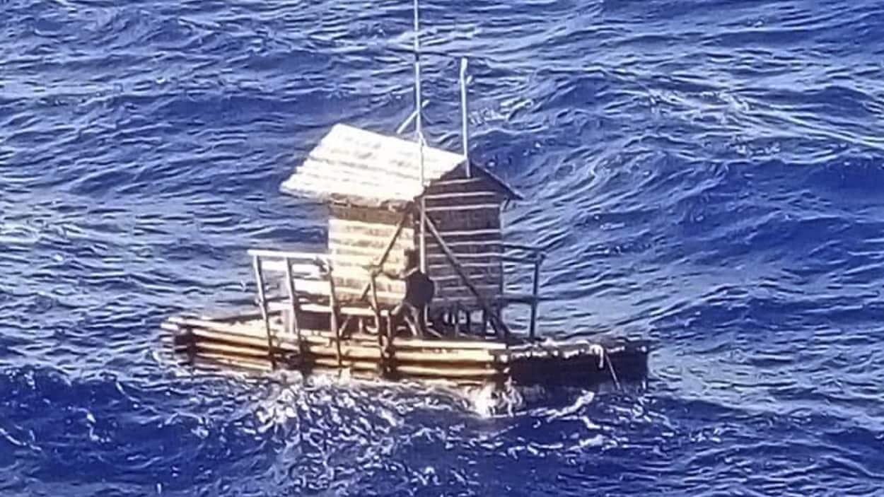 Un individu sur un radeau de bois en pleine mer.