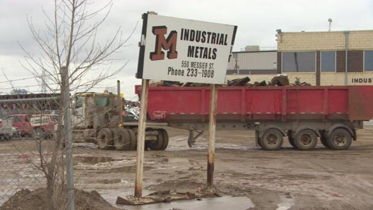 L'avant-plan de la photo montre une affiche de l'usine avec son logo et son adresse. À l'arrière, on voit le bâtiment et un camion transportant des déchets métalliques.
