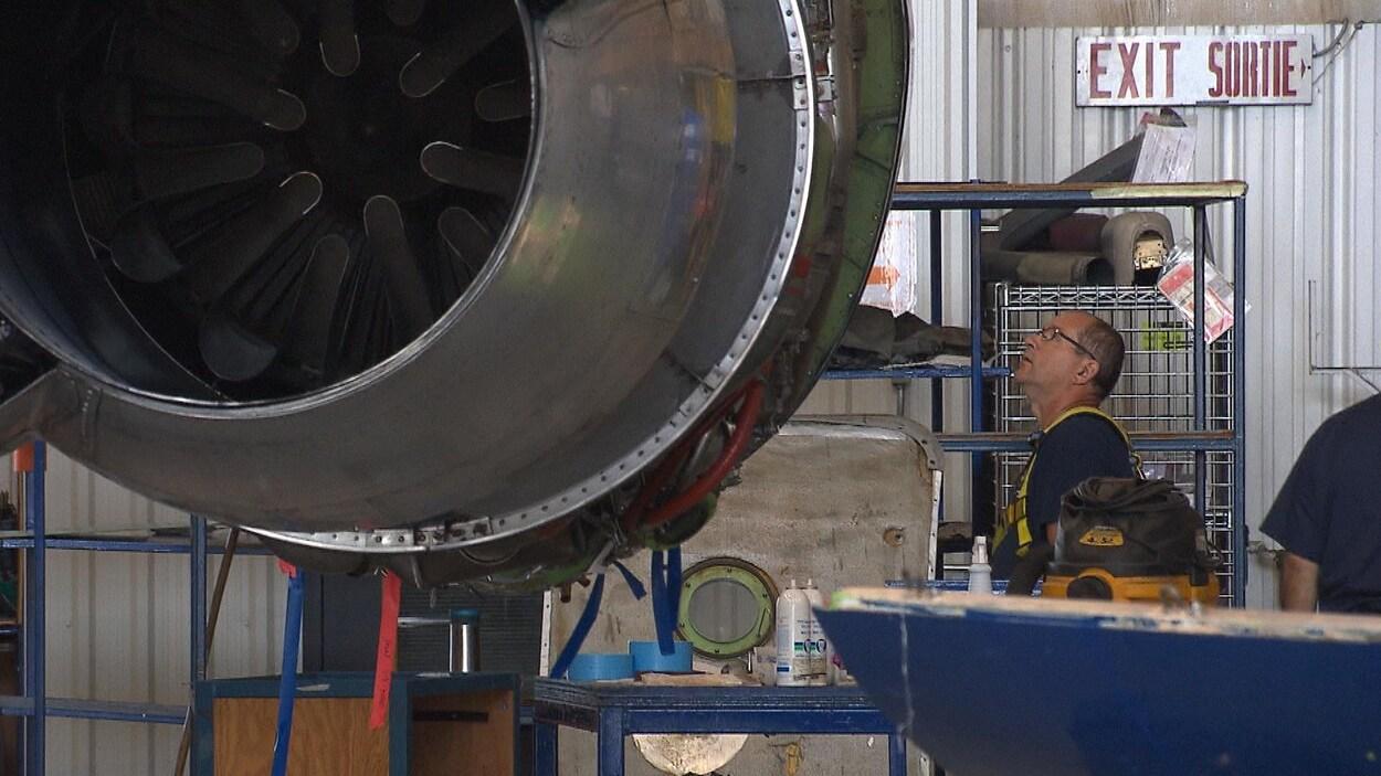 Un employé lève la tête pour regarder la turbine d'un avion.