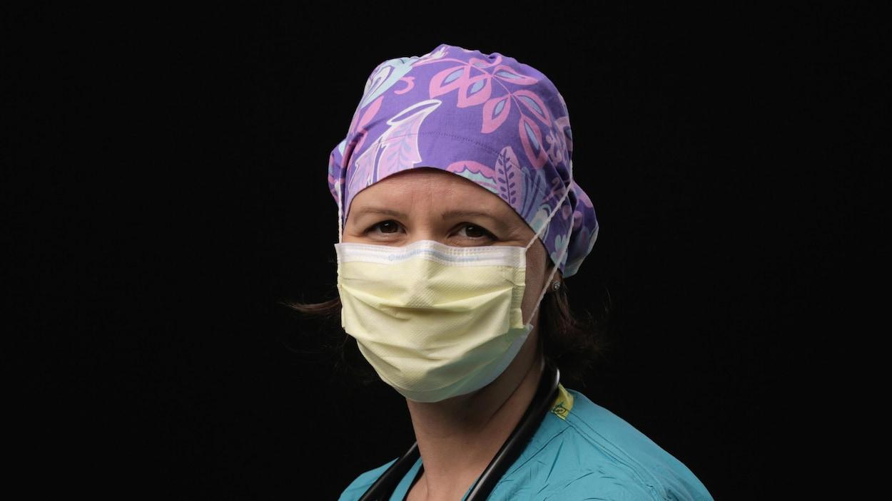 Portrait d'une infirmière portant un masque chirurgical sur le nez et la bouche. Elle porte un foulard en tissu violet et rose sur la tête.