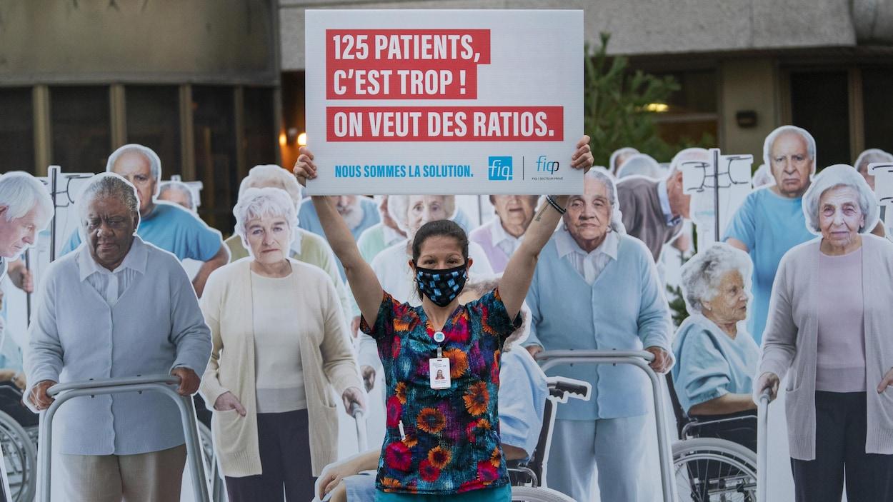 Une membre de la FIQ tenant une pancarte entourée de dizaines d'effigies représentant des patients de CHSLD.