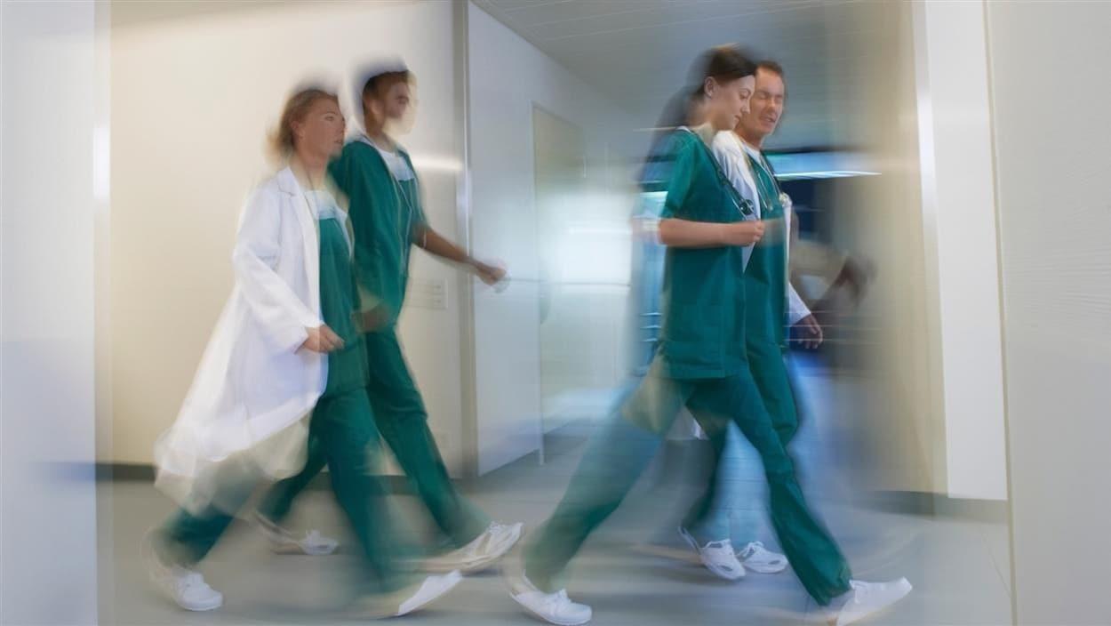 Plan large et flou de quatre travailleurs de la santé marchant dans un corridor d'hôpital.