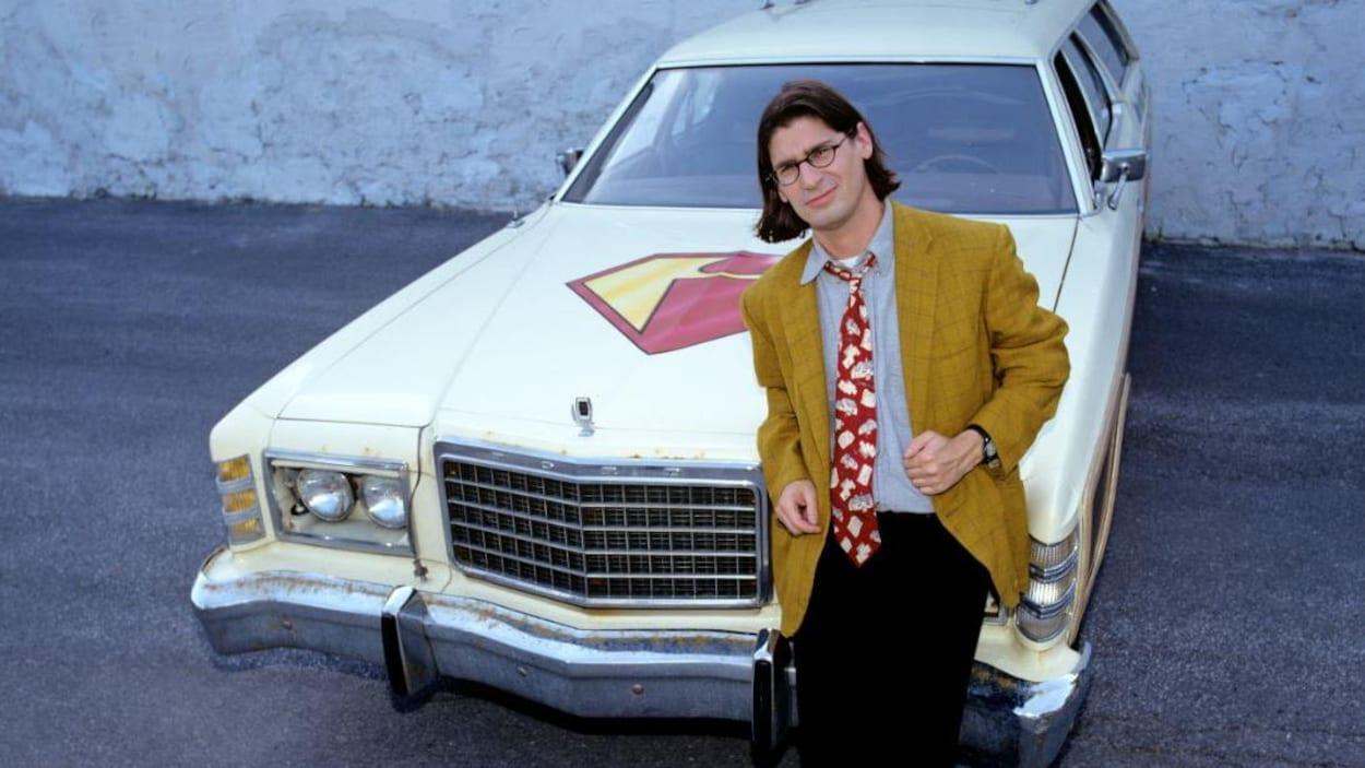 L'homme s'appuie sur le devant d'une voiture affichant le logo d'«Infoman».