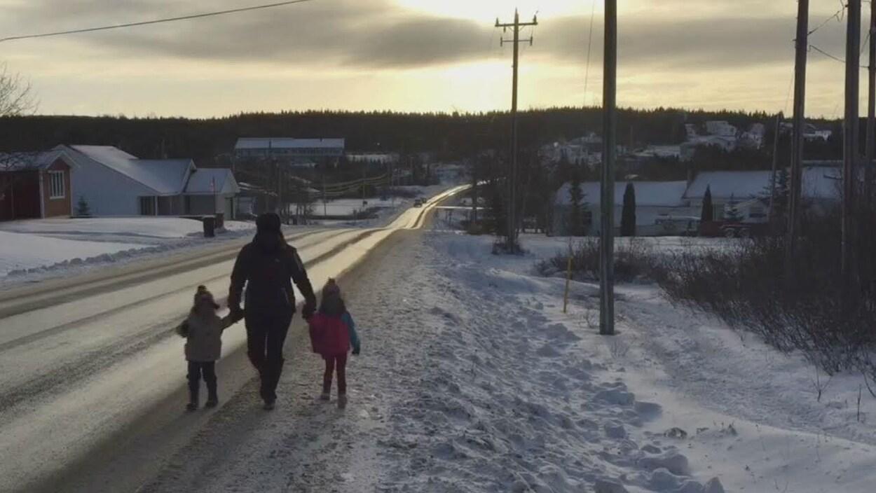 Une femme et deux enfants marchent le long d'une route dans un village en hiver.