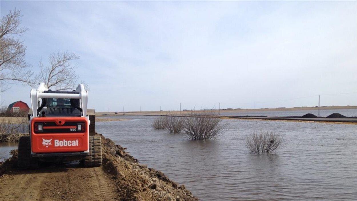 Une petite excavatrice avance sur un chemin de terre surélevé dans un champ inondé.