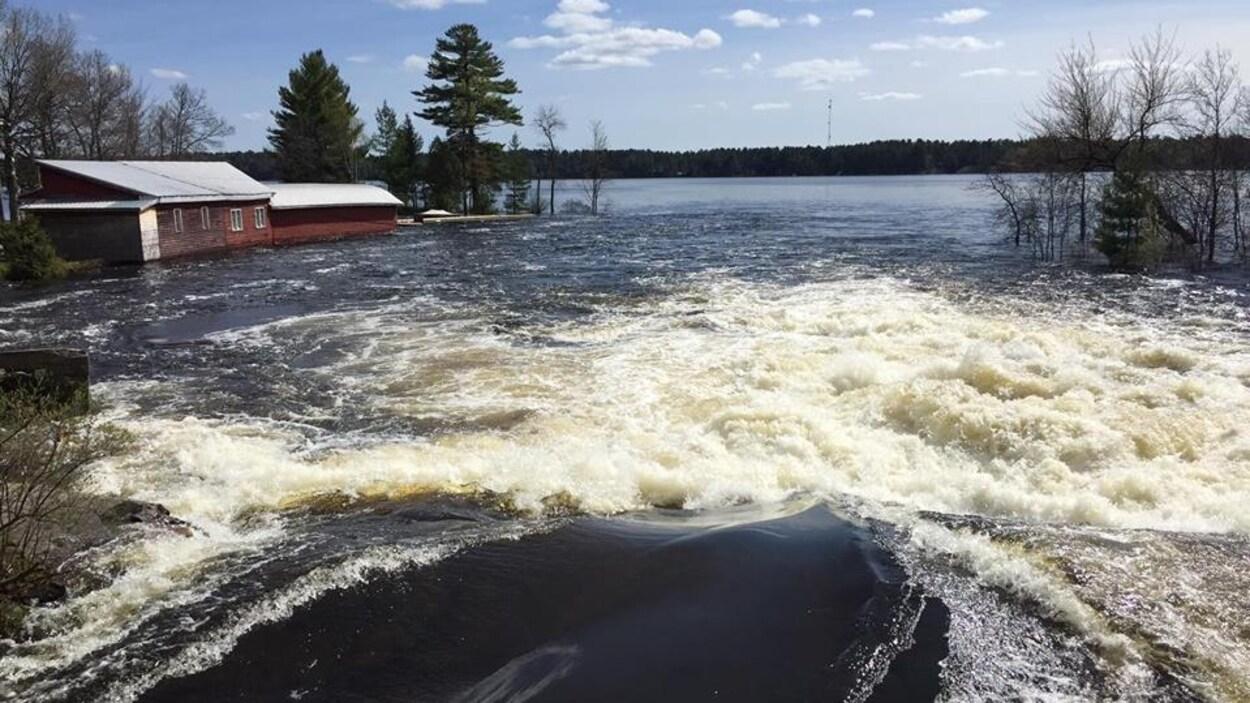 De l'eau qui s'écoule d'un barrage et un bâtiment inondé