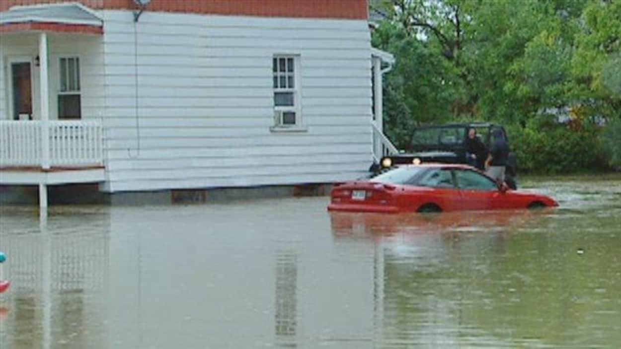 Une maison, une voiture et une Jeep lors des inondations de la rivière Lorette en 2005.
