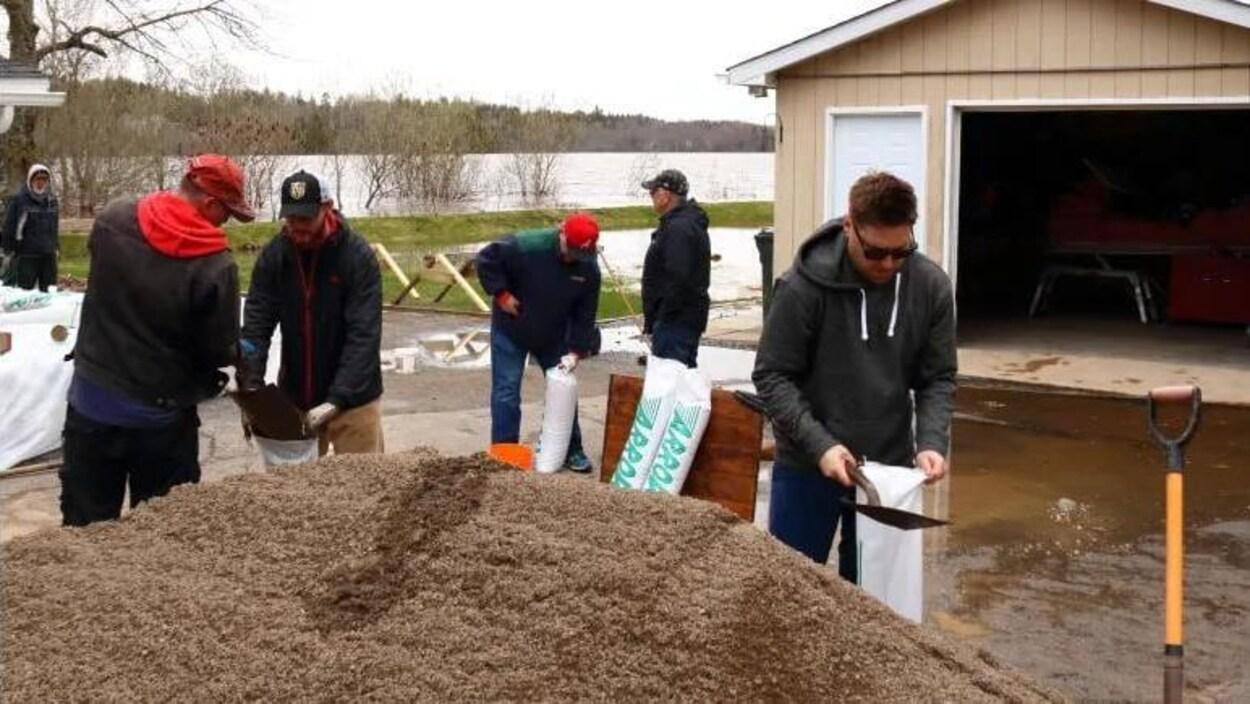 Cinq hommes maniant de petites pelles versent du sable dans des sacs