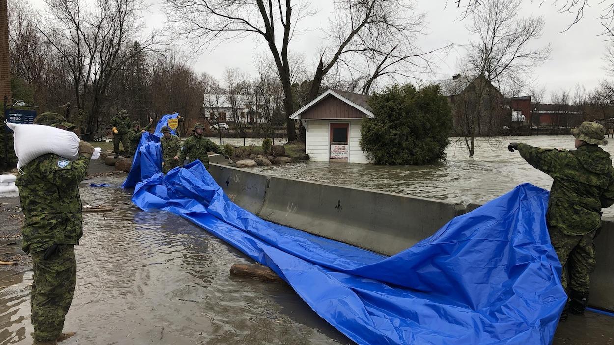 Des militaires construisent une digue.