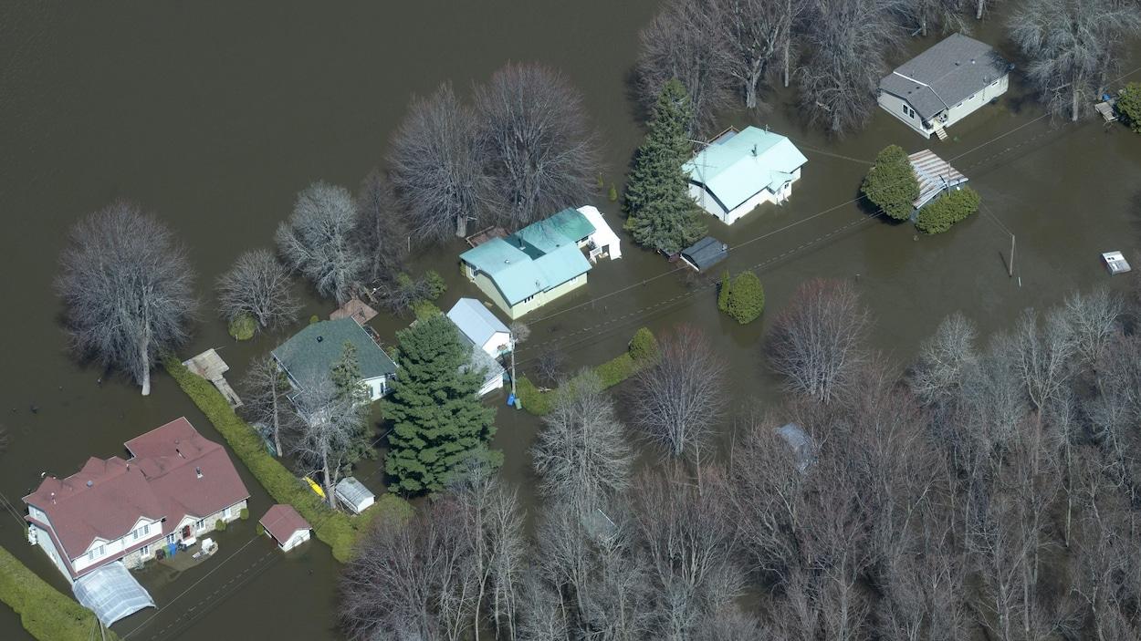 Vue aérienne de cinq maisons complètement entourées d'eau.