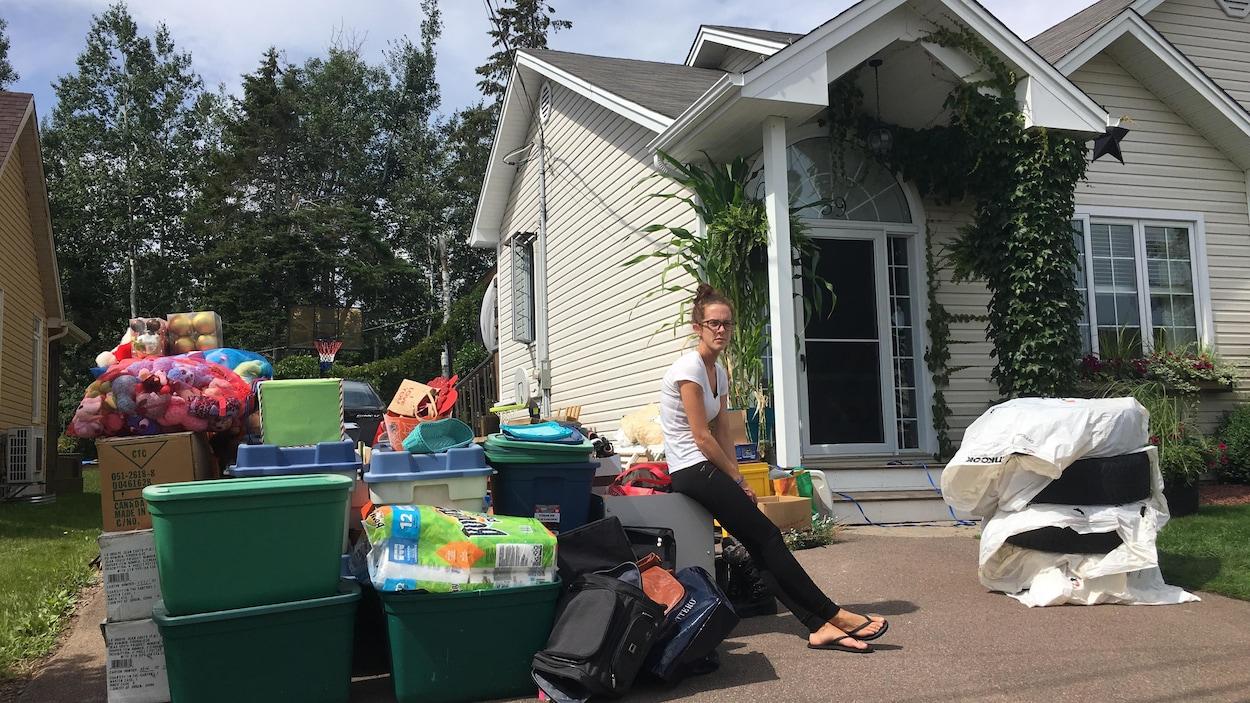 Une femme assise sur ses poubelles.