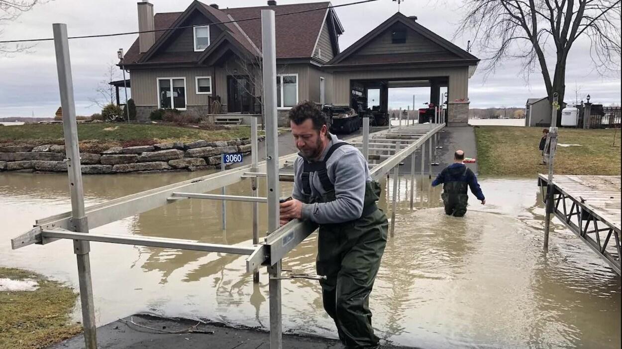 Un homme stabilise une structure en métal reliant la route à une résidence.