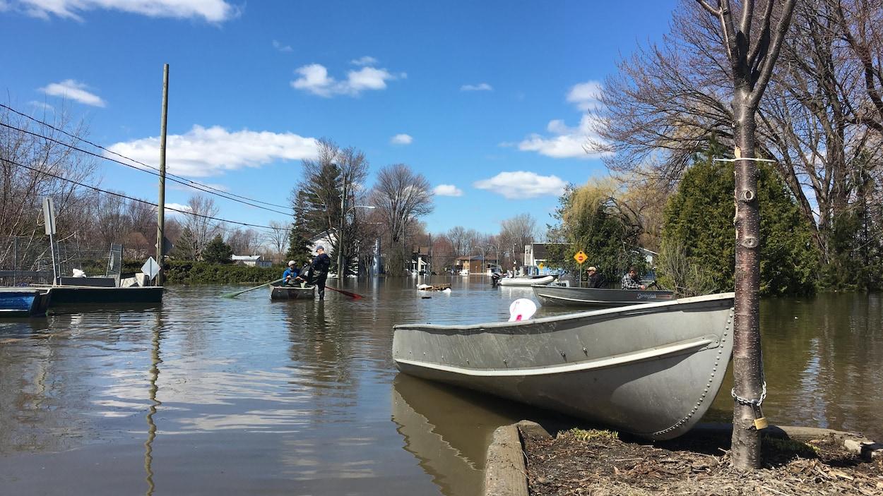 Des embarcations le long d'une rue inondée.