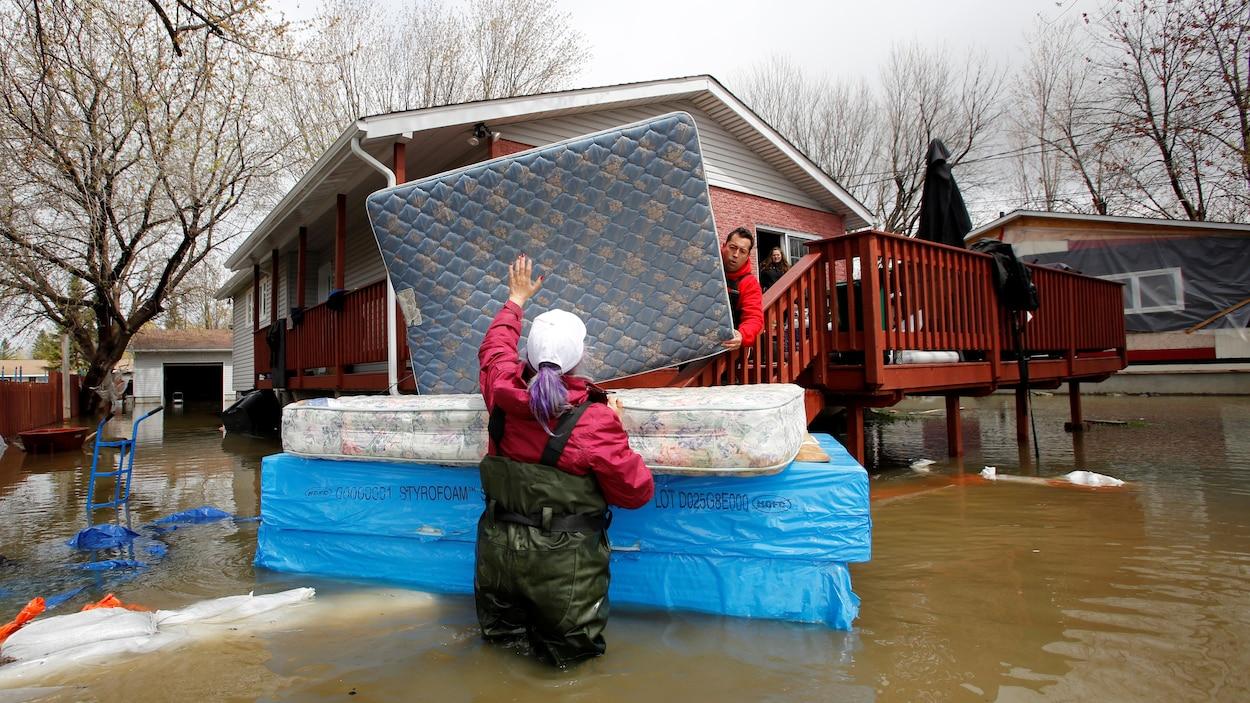 Jean-François Perrault  et Julie Theriault déplacent des matelas d'une résidence inondée d'une maison de Gatineau.