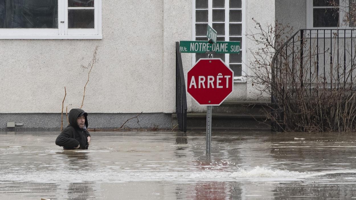 Un homme marche avec de l'eau jusqu'à la taille dans une rue résidentielle. Un panneau d'arrêt se dresse hors des eaux devant une maison.