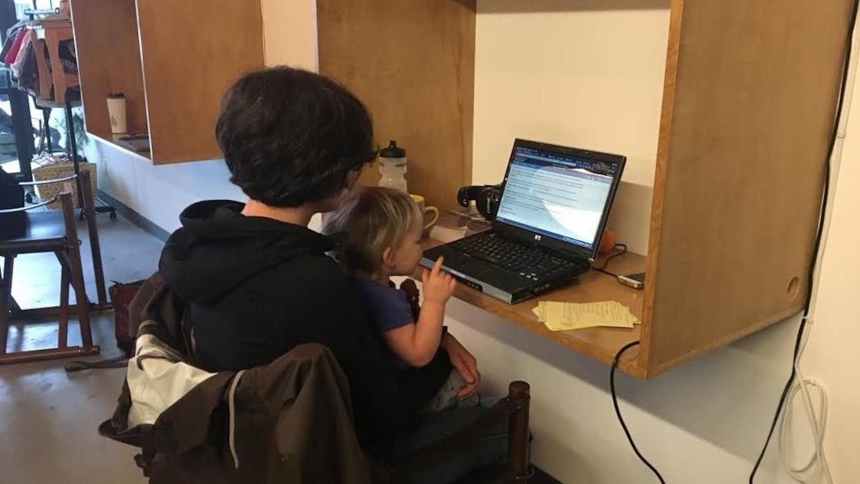 Une femme et sa fille sont de dos devant un ordinateur.