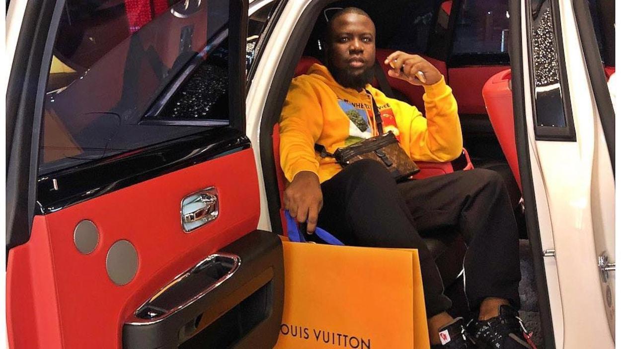 Un homme sur la banquette arrière d'une voiture de luxe avec un sac Louis Vuitton.