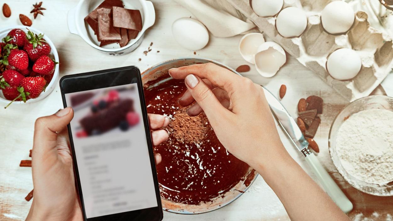 Une personne saupoudre de cacao un gâteau au chocolat en lisant les indications de la recette sur son cellulaire.